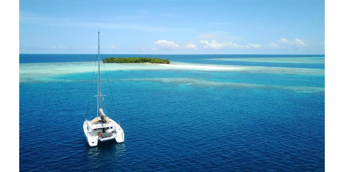 Xl 1200 anchoring in front of a stunning island aboard a maldives catamaran charter elysia yacht charters